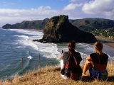 Couple on Bluff Overlooking Black Sand Beach, Piha, New Zealand Photographie par Oliver Strewe