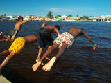 Young Boys Dive Off Marina at Bay of Belize with City in Background, Belize City, Belize Lmina fotogrfica por Anthony Plummer