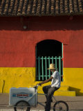 Ice Cream Vendor Riding Bicycle Past Colourful House, Granada, Nicaragua Photographie par Margie Politzer