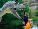 Woman Holding a Girl Up to a Dinosaur Model, Drumheller Valley, Alberta, Canada Photographic Print by Philip & Karen Smith
