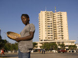 Girl Selling Peanuts on Metical Square, with Highrise Building Behind, Beira, Sofala, Mozambique Photographic Print by Ariadne Van Zandbergen