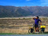 Cyclist Having a Drink on the Side of the Highway between Twizel and Omarama, Otago, New Zealand Photographic Print by Ross Barnett