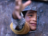 Boy Reaching through Hole in Gate, Alchi, Jammu and Kashmir, India Photographic Print by Daniel Boag