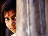 Girl with Forehead Marking Peering from Behind Pillar, Rajasthan, India Photographic Print by Daniel Boag