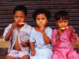 Three Children Eating Icy-Poles, Bengali Basti, Delhi, India Photographic Print by Daniel Boag