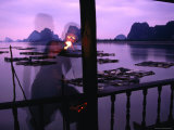 Local Man Lights Pipe Overlooking Net Farms and Karst Formations, Ko Panyi, Phang-Nga, Thailand Photographic Print by Dominic Bonuccelli
