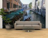 A Gondolier Passes a Restaurant on a Canal in Venice, Italy Wall Mural – Large by Taylor S. Kennedy