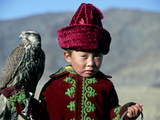 Young Boy Holding a Falcon, Golden Eagle Festival, Mongolia Photographie par Amos Nachoum