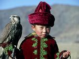 Young Boy Holding a Falcon, Golden Eagle Festival, Mongolia Photographie par Amos Nachoum