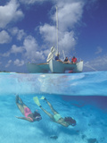 Two Women Snorkeling and People on a Sailboat Photographic Print by Amos Nachoum