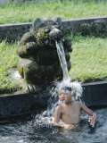 Boy Under a Water Spout, Watertemple, Bali, Indonesia Photographic Print by Gavin Hellier