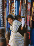 Woman and Baby, Cloth Shopkeeper in Temple Square, Bodhnath, Kathmandu, Nepal Photographic Print by Anthony Waltham