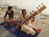 Musicians Playing the Sitar and Tabla on the Banks of the River Ganges, Varanasi, India Papier Photo par John Henry Claude Wilson