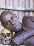 Portrait of an Asmat Tribesman Leaning on a Human Skull, Irian Jaya, Indonesia Photographic Print by Claire Leimbach