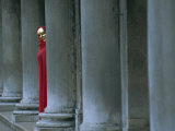 Carnival Model in Red Cape and Gold Mask Peering from Columns in St. Mark's Square, Veneto, Italy Photographic Print by Lee Frost