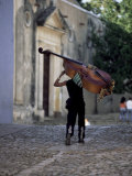 Musician Carrying Double Bass Along Cobbled Street to Plaza Mayor, Trinidad, Cuba Fotografisk tryk af Lee Frost