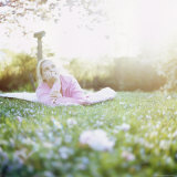 Woman Relaxing on Lawn Surrounded by Cherry Blossom, Washington State, USA Photographic Print by Aaron McCoy