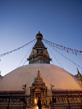 A Monk Lights Butter Lamps on Gilded Shrine at Base of Stupa at Dawn, Nepal Photographic Print by Don Smith