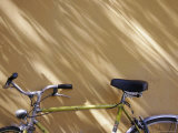 Bicycle Leaning against a Shadowed Yellow Wall, Parma, Italy Photographic Print by Gina Martin