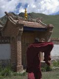 Buddhist Monk in a Windswept Robe, Nears a Brick Gate, Qinghai, China Photographic Print by David Evans