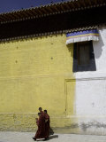 Buddhist Monks Walk Next to a Yellow and White Building, Qinghai, China Photographic Print by David Evans