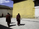 Buddhist Monks Crossing a Street near a Yellow and White Building, Qinghai, China Photographic Print by David Evans