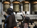 Buddhist Woman and Child Spin Brass Prayer Wheels, Qinghai, China Fotografisk tryk af David Evans