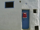 Child&#39;s Dress Hangs in Front of a Blue Door in a Whitewashed House Photographic Print by James L. Stanfield
