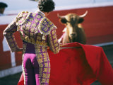 Bullfighter Holds his Red Cape Before a Bull Fotografie-Druck von Pablo Corral Vega