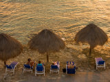 Guests Relax at Sunset Along the Water at the Caribe Blu Hotel, Cozumel, Mexico Photographic Print by Michael S. Lewis