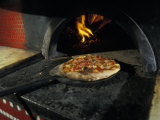 Pizza Comes Out of a Brick Oven in a Restaurant in Rome, Italy Photographic Print by Richard Nowitz