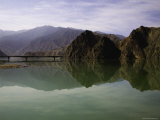 Reflections of a Bridge and Mountains in the Quiet Yellow River, Qinghai, China Photographic Print by David Evans