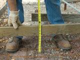 Man Measures a Wood Frame Before Pouring Concrete Photographie par Joel Sartore