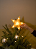 Placing a Star on a Christmas Tree Photographic Print by John Burcham