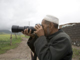 Muslim Rural Resident Looks Through a Camera, Qinghai, China Photographic Print by David Evans