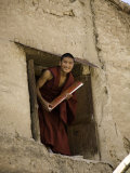 Monk in a Dormitory Window with a Book, Qinghai, China Photographic Print by David Evans