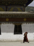 Monk Shields his Head from the Sun Walking Past a Painted Building, Qinghai, China Photographic Print by David Evans