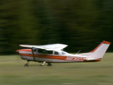 Pan Blur of a Small Bush Plane Landing in a Meadow, Alaska Photographic Print by Kate Thompson