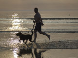 Silhouette of Man Running with Dog on Beach, Sunset, Romo, Denmark Photographic Print by  Brimberg & Coulson