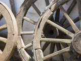 Old Wooden Wagon Wheels Leab against a Whitewashed Wall Photographic Print by David Evans