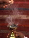 Two Hands Burn Traditional Spices in Front of a Decorative Cloth in Petra, Jordan Photographic Print by Richard Nowitz
