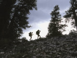 Two Hikers Ascend a Rocky Ridge Among Pines Photographic Print by Dawn Kish