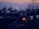 Trains Surrounded by Industrial Plants Photographic Print by Kenneth Garrett