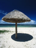 Thatch Palapa Umbrella on Beach with People Walking Next to the Sea Photographic Print by James Forte