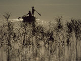 Silhouetted Figures Ply a Small Rowboat on the Calm Surface of the Lake Photographic Print by James L. Stanfield