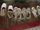 Various Pairs of Shoes Hang on a Wire Fence Photographic Print by James L. Stanfield