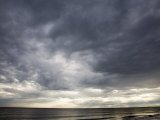Sun Streams Through Gathering Storm Clouds on North Carolina Coast Photographic Print by David Evans