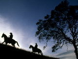 Silhouette of a Man and Woman Riding their Horses Up a Grassy Hill Photographic Print by Kate Thompson