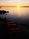 Two Empty Wooden Chairs Sit on Maine's Rocky Coast as the Sun Sets over the Horizon Photographic Print by Tim Laman