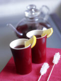 Two Beakers of Fruit Tea with Lemon Wedges, Sugar Sticks Fotografie-Druck von Anita Oberhauser